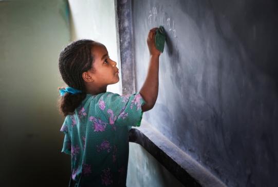 Eine Schülerin schreibt an die neue Tafel einer gerade eröffneten MfM-Schule.
