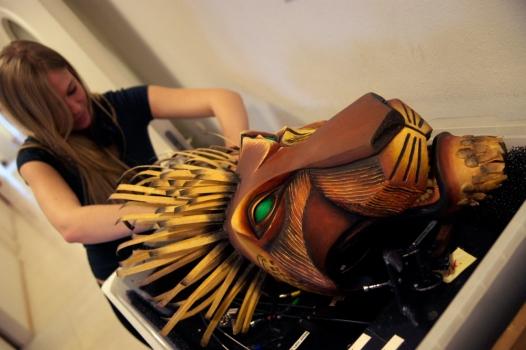 Eine Technikerin kalibriert die aufwändige Maske des Löwen-Fieslings Ska