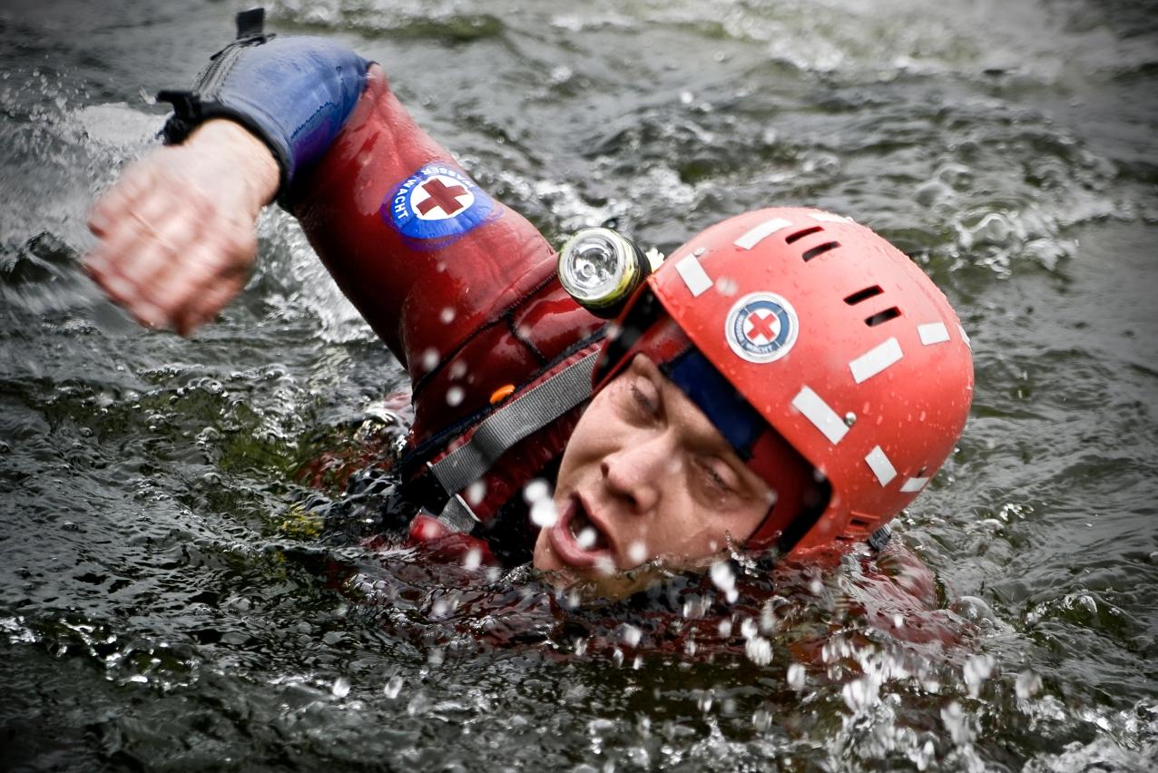 Schwimmen lernen vom Wasserretter: Goldenbogen mit Neoprenanzug und Helm.